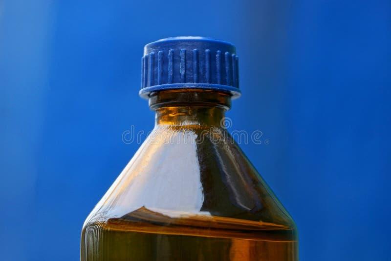 Een fragment van een kleine glas bruine die fles door cork op een blauwe achtergrond wordt gesloten royalty-vrije stock foto's