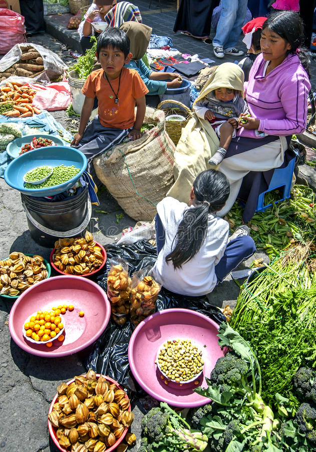 Een fruit en een plantaardige verkoper met haar kinderen bij de Indische markt in Otavolo in Ecuador royalty-vrije stock foto's
