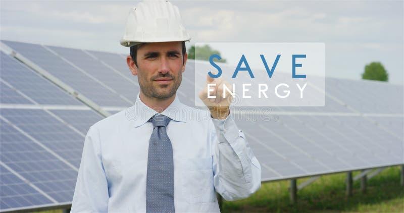 Een futuristische technische deskundige in zonne photovoltaic panelen, selecteert ` sparen energie` functie gebruikend zuivere du royalty-vrije stock fotografie