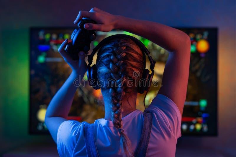 Een gamer of een wimpelmeisje thuis in een donkere ruimte met een gamepad die met vrienden op de netwerken in videospelletjes spe stock foto's