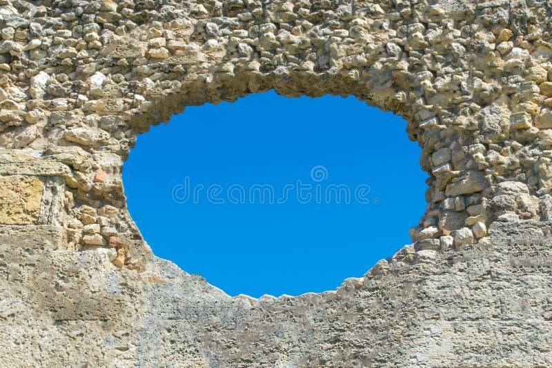 Een gat in de steenmuur en de blauwe hemel op de achtergrond, een geru?neerde muur met een gat royalty-vrije stock afbeeldingen