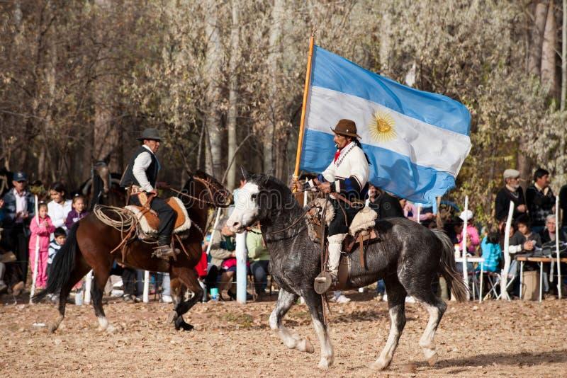 Een Gaucho met Argentijnse vlag die een paard in e berijdt