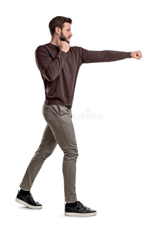 Een geïsoleerde gebaarde mens in vrijetijdskleding bevindt zich in een zijaanzicht en slaat lege lucht met één wapen stock foto