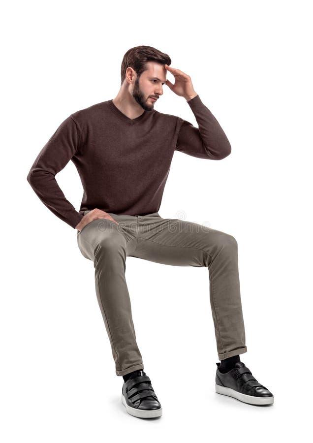 Een geïsoleerde gebaarde mens in vrijetijdskleding zit op een witte achtergrond met één hand wat betreft zijn voorhoofd stock foto