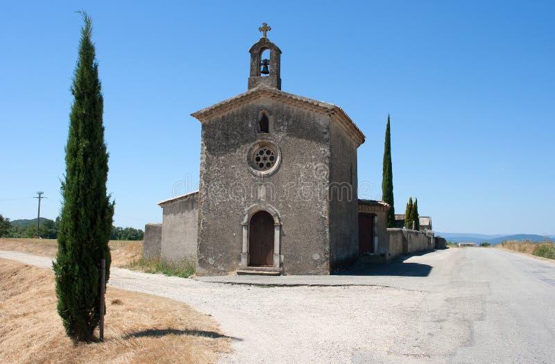 Een geïsoleerde kleine Katholieke Kerk met klokketoren en opgezet kruisbeeld op het Drome-gebied van Zuidoostenfrankrijk stock fotografie