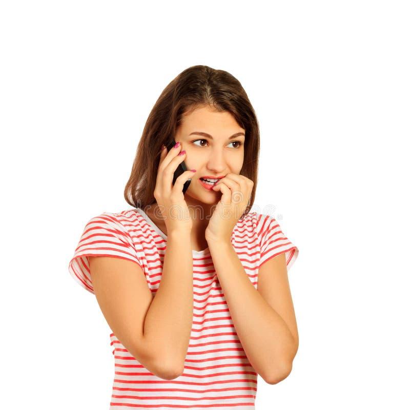Een geageerd verstoord zenuwachtig meisje bijt haar spijkers, houdt een moderne smartphone, voelt verstoord emotioneel die meisje royalty-vrije stock afbeeldingen