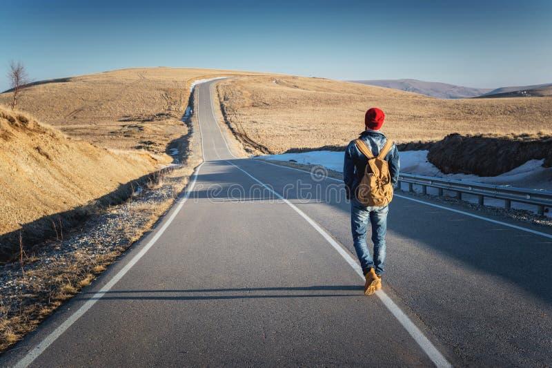 Een gebaarde hipster met een ouderwetse uitstekende rugzak die zonnebril met een rood hoed en jeansjasje en jeans dragen royalty-vrije stock fotografie