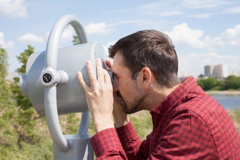Een gebaarde mens kijkt door openbare verrekijkers stock foto