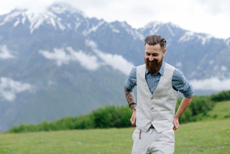 Een gebaarde mens kleedde zich in kostuum op de achtergrond op bergen De zomer in Georgië royalty-vrije stock foto