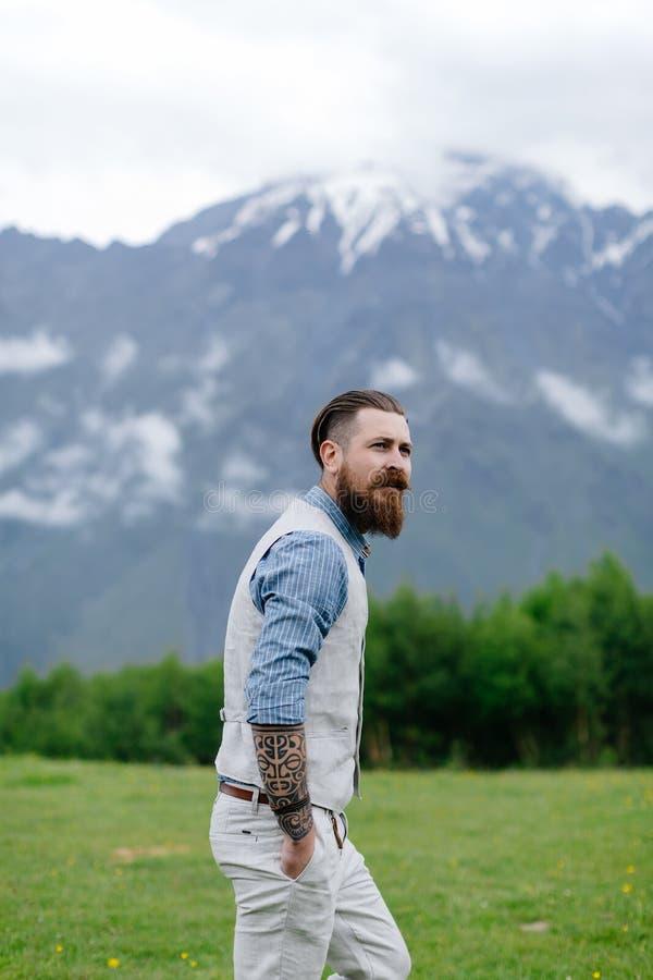Een gebaarde mens kleedde zich in kostuum op de achtergrond op bergen De zomer in Georgië stock foto