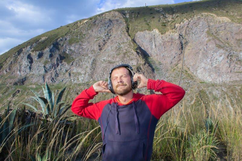 Een gebaarde mens luistert aan muziek op hoofdtelefoons, in aard Achter hem zijn bergen Hij is gelukkig stock afbeeldingen