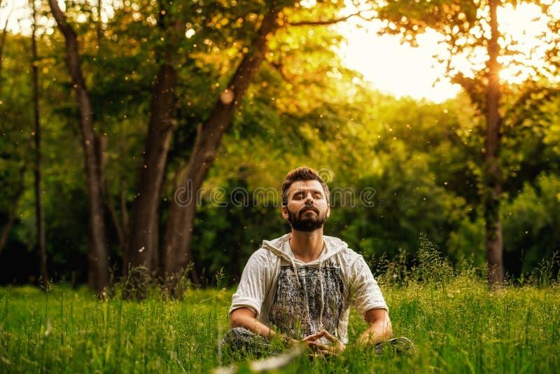 Een gebaarde mens mediteert op groen gras in het park royalty-vrije stock afbeelding