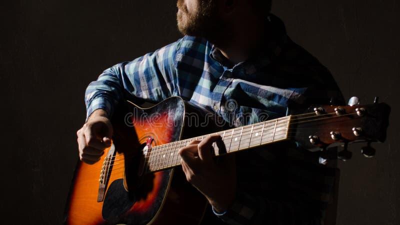 Een gebaarde mens in een plaidoverhemd speelt een akoestische gitaar Het proces van spijkers stock foto