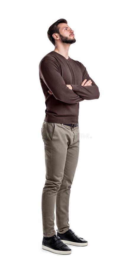 Een gebaarde mens in slimme vrijetijdskleding bevindt zich in helft-draai met gevouwen wapens en kijkt upwards royalty-vrije stock foto