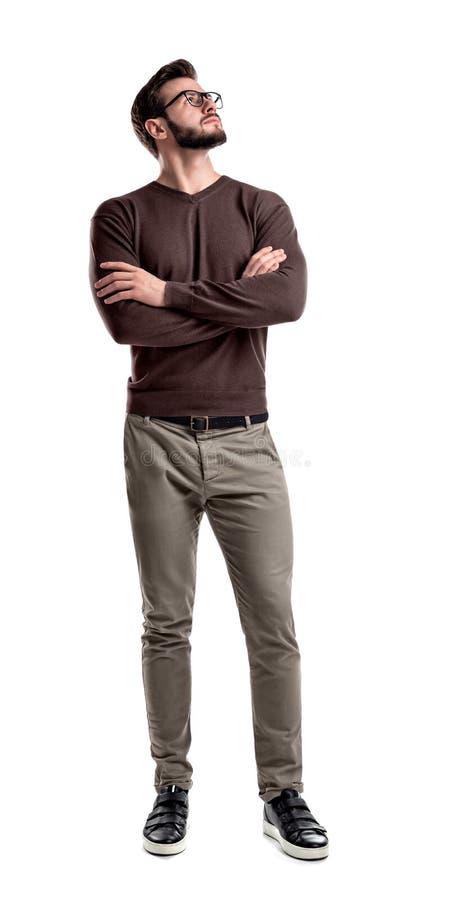 Een gebaarde mens in slimme vrijetijdskleding kijkt kant omhoog met zijn die wapens op zijn borst worden gevouwen royalty-vrije stock foto's