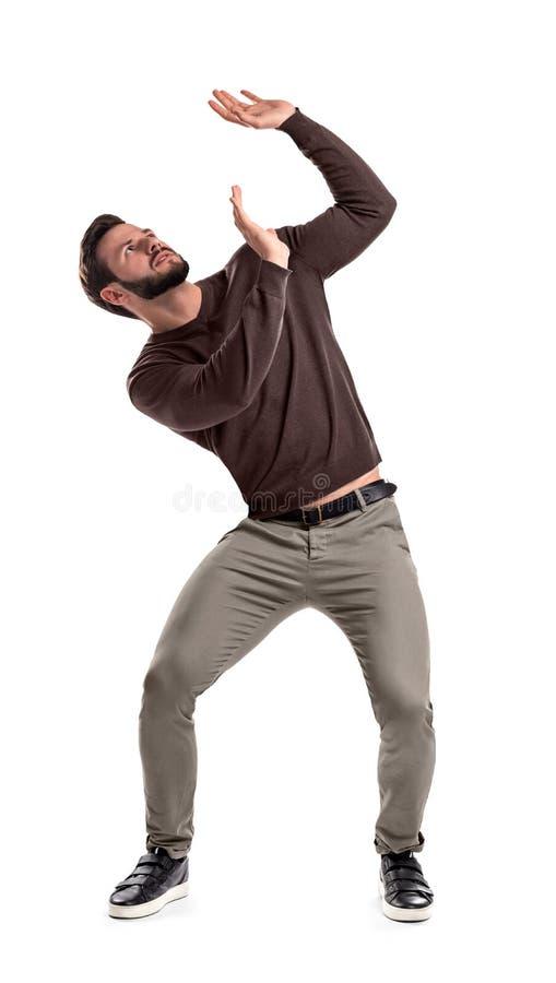 Een gebaarde mens in toevallig gewaad bevindt zich beschermend met uitgestrekte handen tegen iets die aan hem hierboven worden va royalty-vrije stock afbeelding