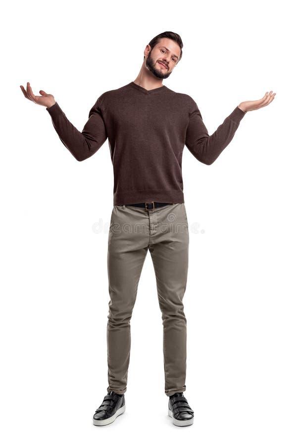 Een gebaarde mens in vrijetijdskleding bevindt zich met beide wapens omhoog en een het vragen gezichtsuitdrukking stock afbeeldingen