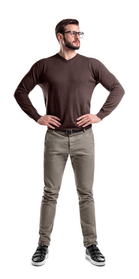 Een gebaarde mens in vrijetijdskleding bevindt zich met handen op zijn die heupen op een witte achtergrond worden geïsoleerd royalty-vrije stock afbeelding