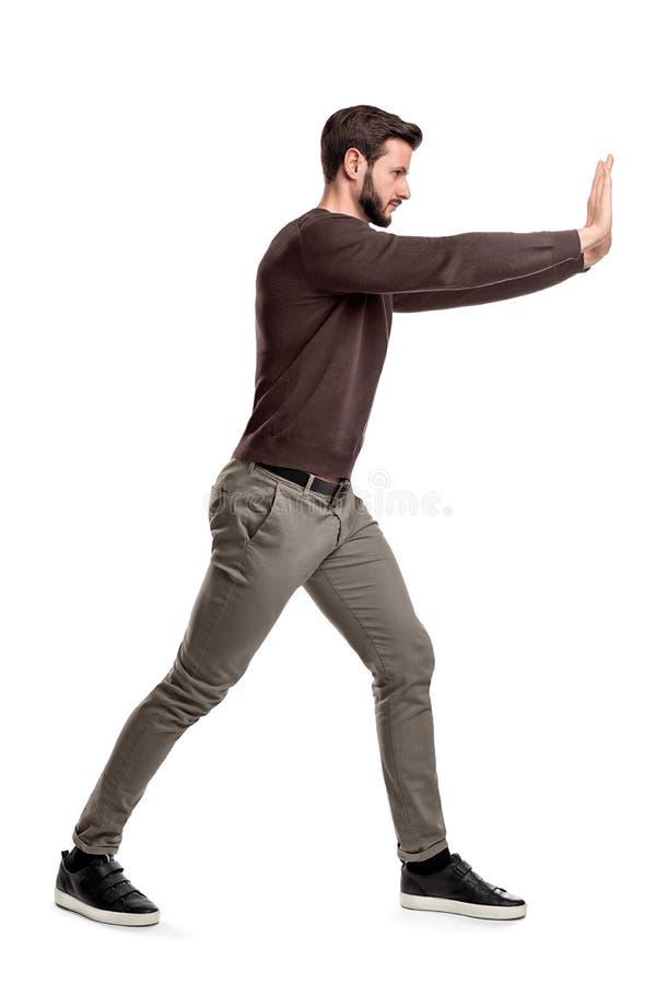 Een gebaarde mens in vrijetijdskleding probeert om een zwaar voorwerp met beide wapens met één been te duwen gezet vooraan voor s stock foto's