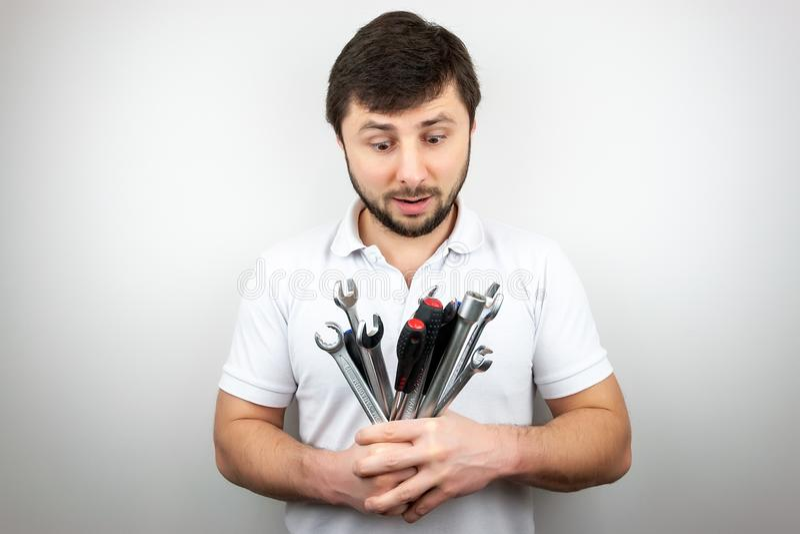 Een gebaarde mens in een witte t-shirt bekijkt verrast een boeket van moersleutels en schroevedraaiers stock foto