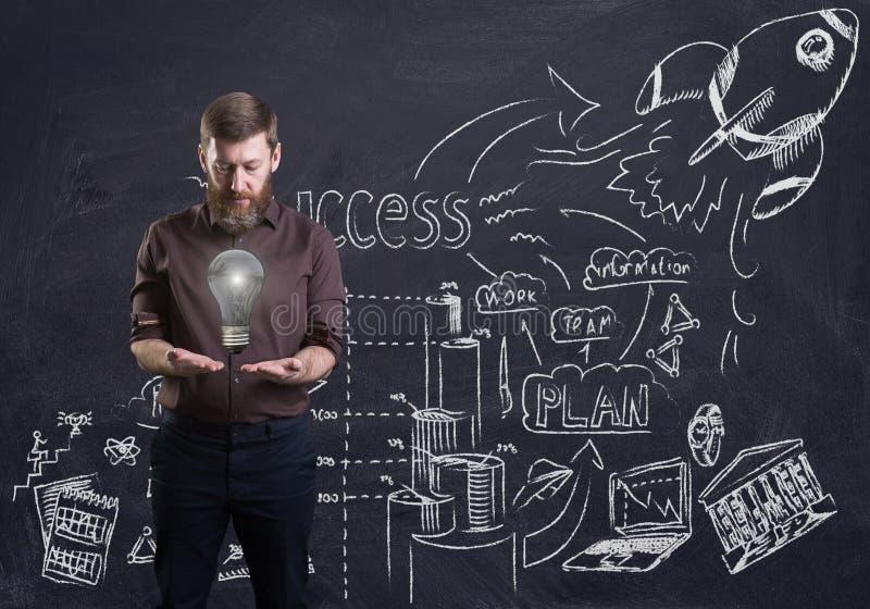 Een gebaarde zakenman die een gloeilamp houden Bedrijfskrabbels die op een bord erachter worden getrokken 3d geef elementen in co stock fotografie