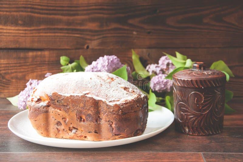 Een gebakken eigengemaakte die cake met poeder wordt bestrooid bevindt zich op een raad dichtbij een kleine kleipot stock foto's