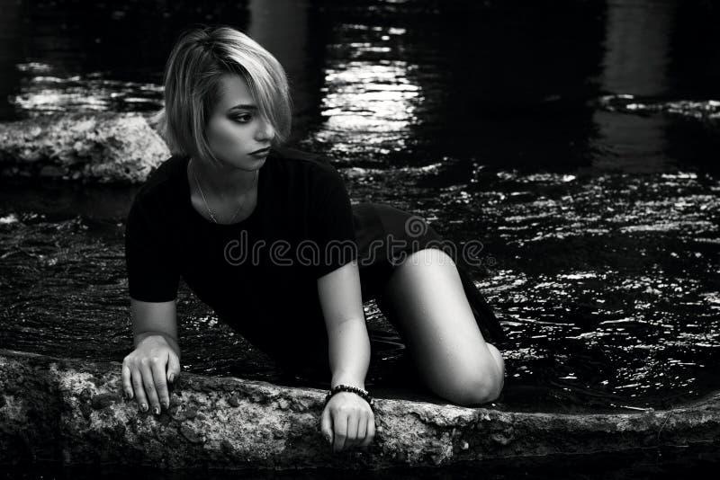 Een gebegeerd sexy meisje in een zwarte kleding die, passionately in stellen royalty-vrije stock afbeeldingen