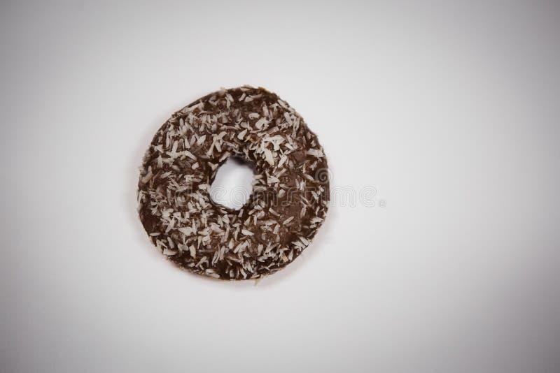 Een gebeten doughnut ligt op een witte achtergrond stock fotografie