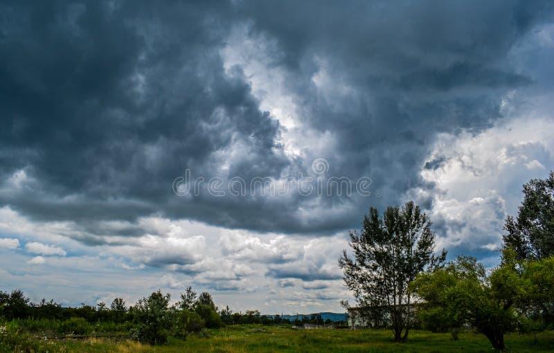 Een gebied van groene bomen en een hemelhoogtepunt van zwarte, het dreigen betrekken Het sterke onweer begint royalty-vrije stock fotografie