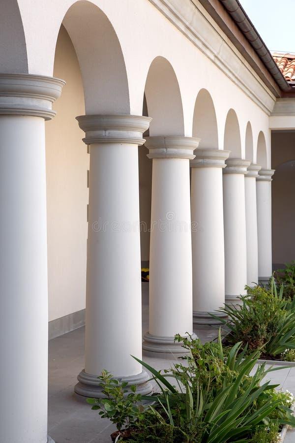 Een gebouw met kolommen en overspannen openingen bij het gebouw met bloembedden royalty-vrije stock foto