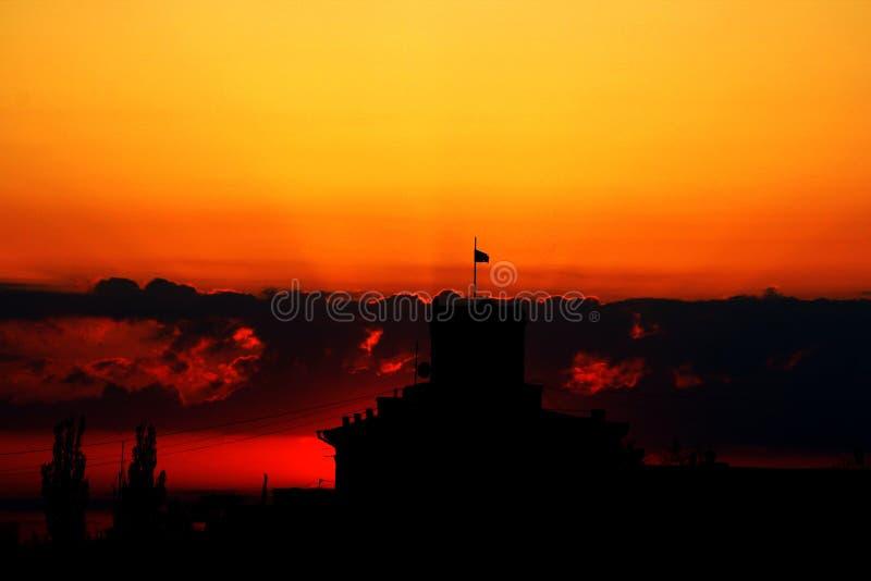Een gebouw met een toren en een vlag op het tegen de zonsonderganghemel stock foto's