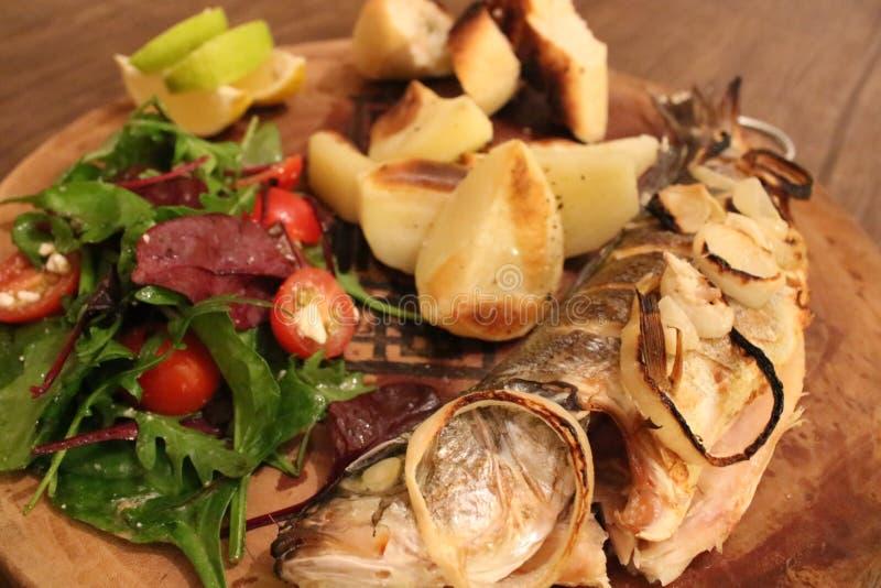 Een gebraden vis met salade stock foto's