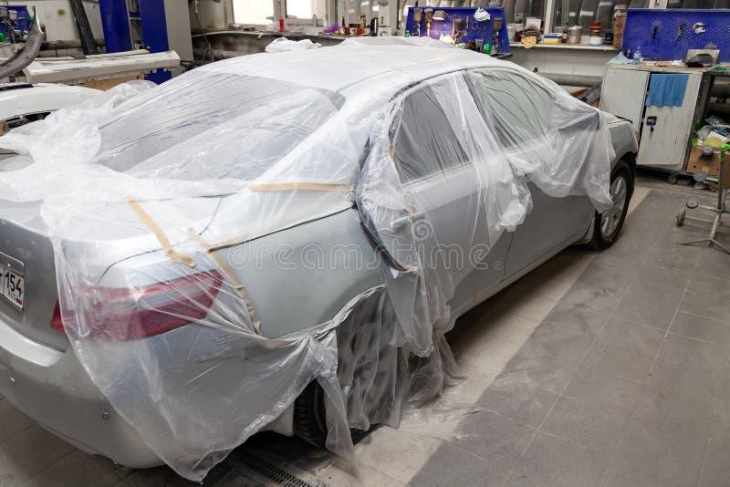 Een gebroken die auto met een beschermende film van het bespatten van verf in een nevelcabine wordt behandeld in een reparatiewer stock afbeeldingen