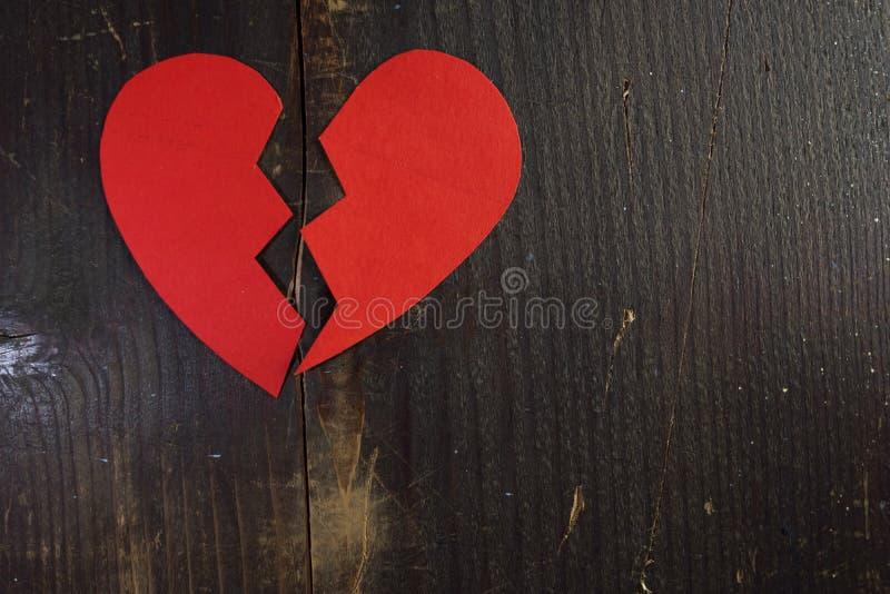 Een gebroken gescheurd hart van rood document op een ruwe houten achtergrond royalty-vrije stock afbeeldingen