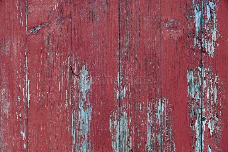Een gebroken ziekelijke houten muur met oude rode verf stock afbeelding