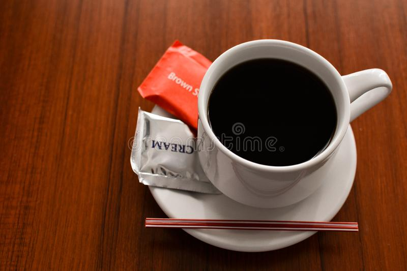 Een gebrouwen koffie in een witte kop met suiker en roomkan een lijst stock afbeelding
