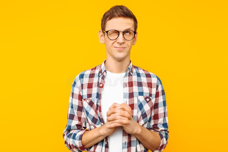 Een geconcentreerde mens met glazen, een mens in een plaidoverhemd, dat van hem vouwde dient gebed in, vraagt om zijn behoefte op stock afbeeldingen