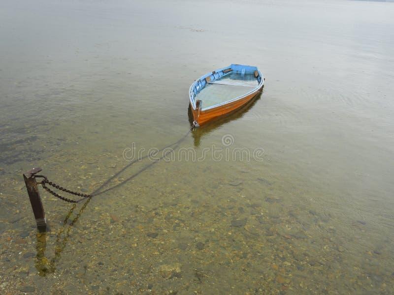 Een gedaalde houten boot in een transparant meer stock foto