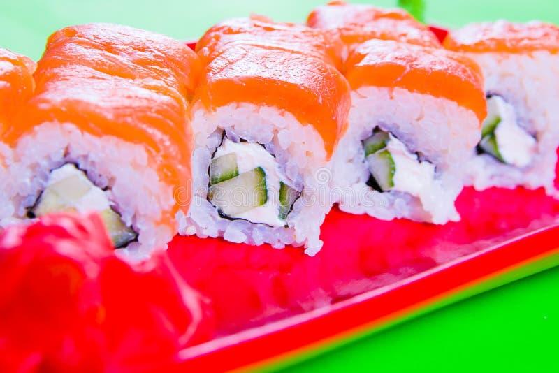 Een gedeelte sushi op een rode plaat Groene Achtergrond royalty-vrije stock foto's