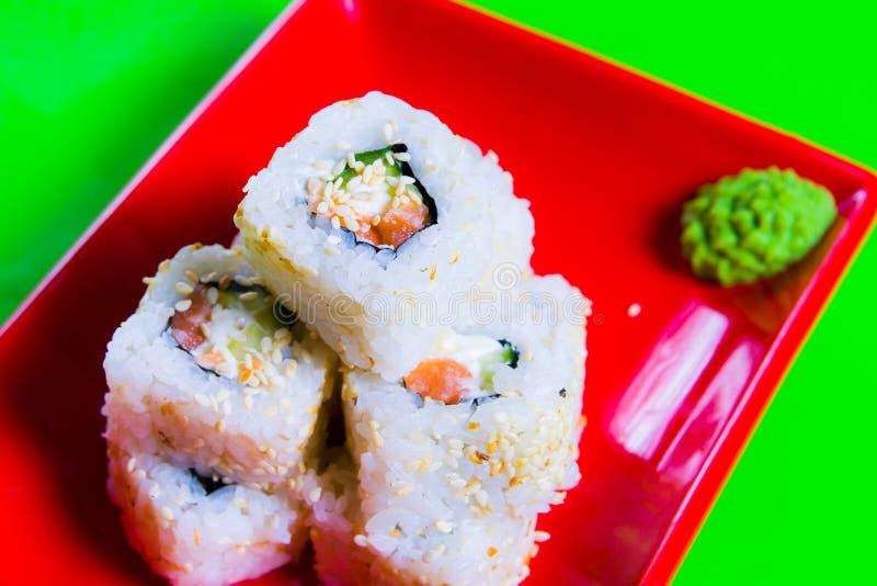 Een gedeelte sushi op een rode plaat Groene Achtergrond royalty-vrije stock foto