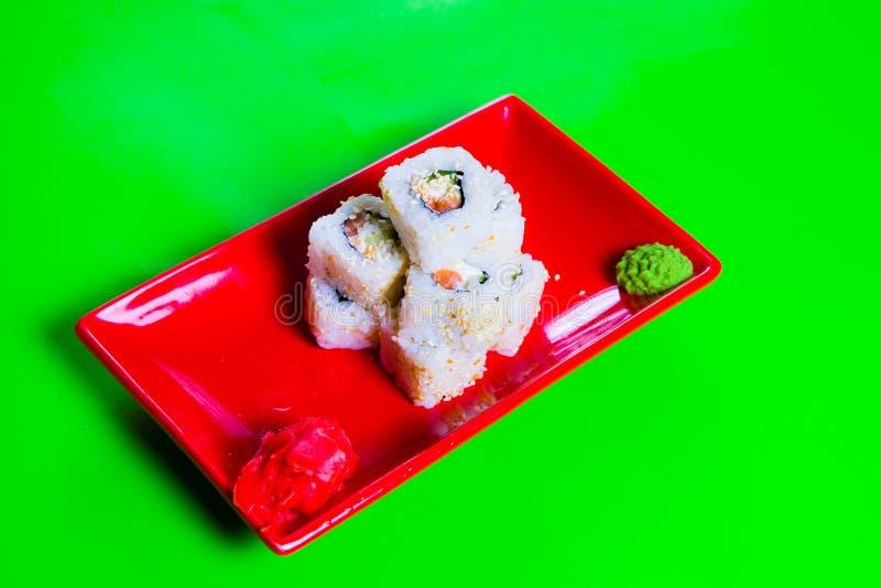Een gedeelte sushi op een rode plaat Groene Achtergrond stock afbeelding