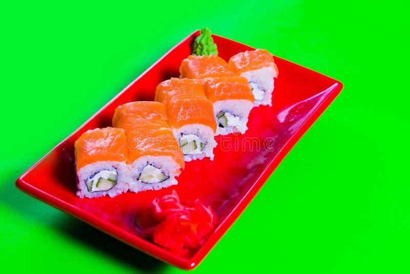 Een gedeelte sushi op een rode plaat Groene Achtergrond royalty-vrije stock afbeelding