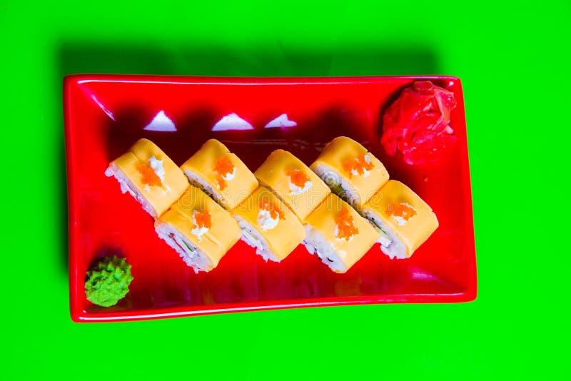 Een gedeelte sushi op een rode plaat Groene Achtergrond stock foto's