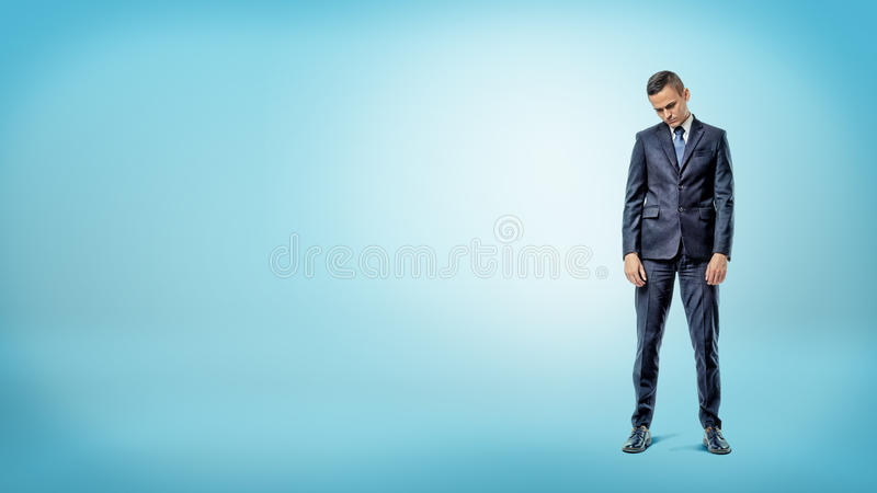 Een gedeprimeerde zakenman die zich met schouders bevinden stortte op blauwe achtergrond in stock fotografie