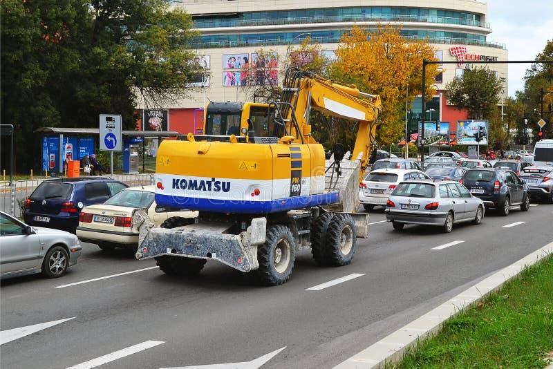 Een geel graafwerktuig of buldozer met weels op een stadsstraat onder auto's op een dag stock foto's