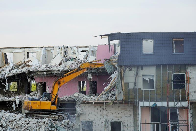 Een geel graafwerktuig vernietigt een gebouw met meerdere verdiepingen met een gietlepel De techniek vernietigt het gebouw, is mo stock fotografie