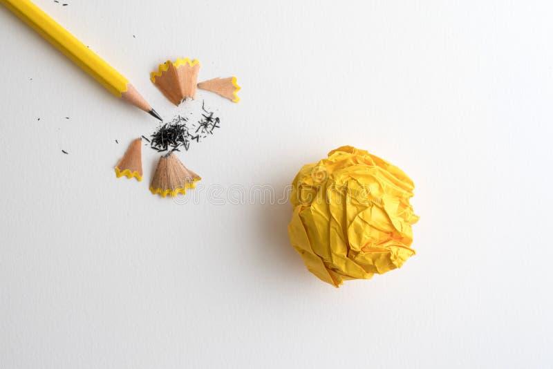 Een Geel potlood en een geel verfrommeld document met het scheren op wit royalty-vrije stock foto's