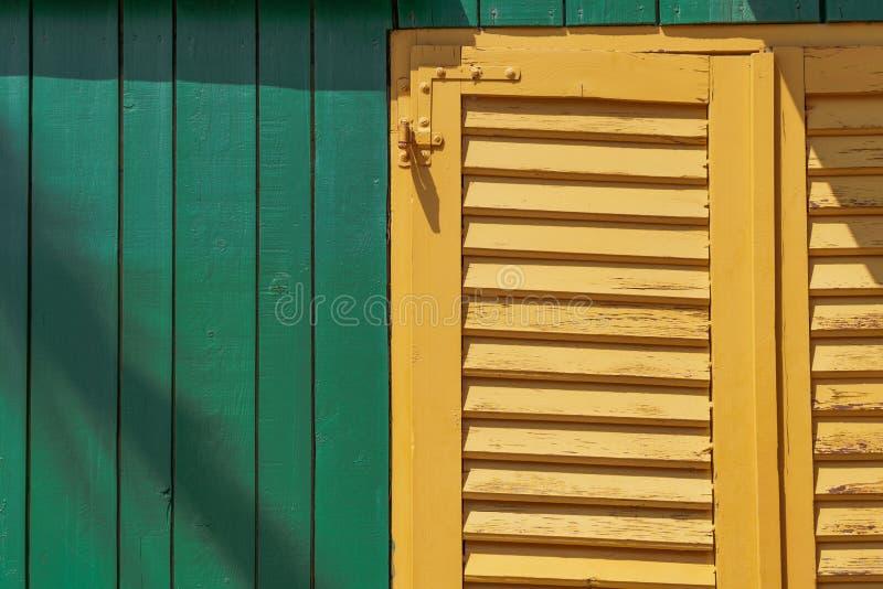 Een geel venster op een groene loods stock foto