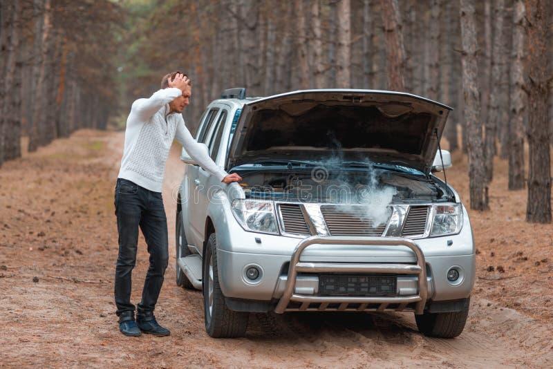 Een gefrustreerde kerel, die zich dichtbij een gebroken auto met een open kap met rook bevinden, bevindt zich en houdt hoofd stock afbeeldingen