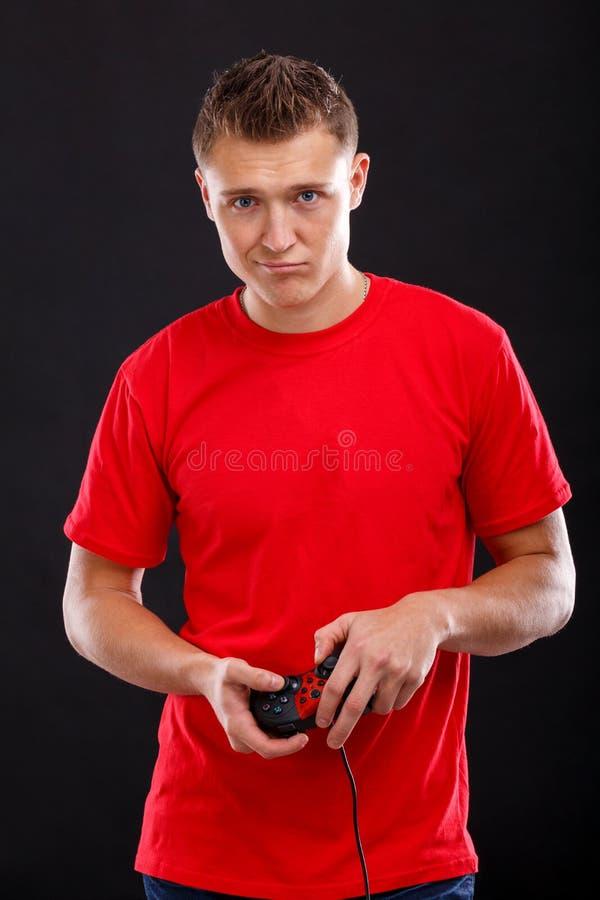 Een gefrustreerde kerel gekleed in een rode T-shirt, houdt een spelbedieningshendel Op een zwarte achtergrond stock afbeelding